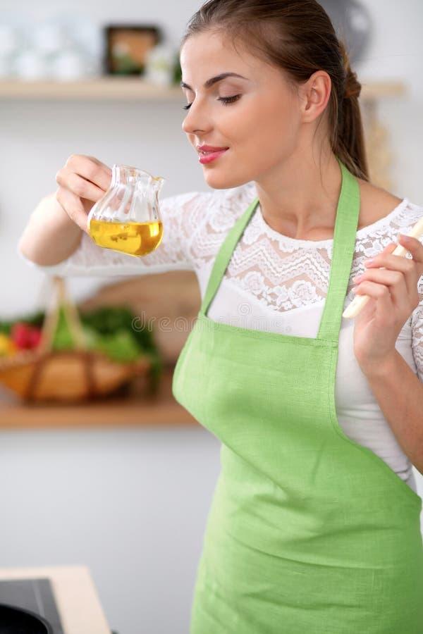 Jovem mulher no avental verde que cozinha na cozinha Dona de casa que cheira o óleo quando apreciar prepairing a salada imagem de stock