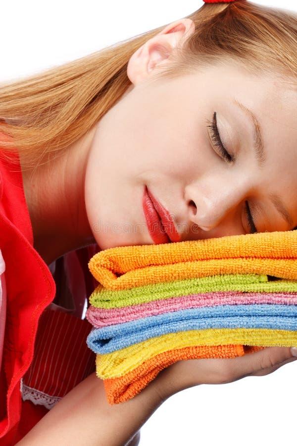 Jovem mulher no avental vermelho que dorme na pilha de toalhas de chá coloridas fotografia de stock royalty free