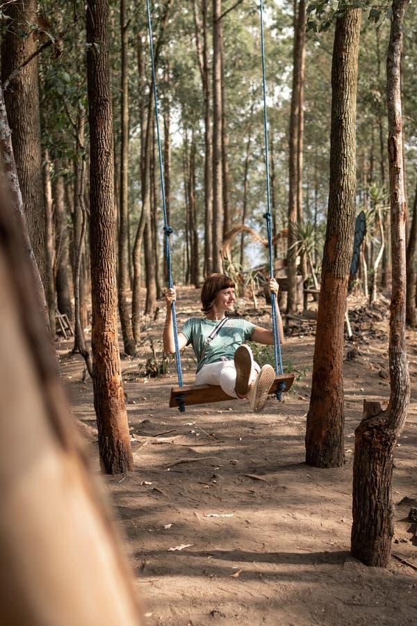 Jovem mulher no balanço na ilha de Bali da floresta imagem de stock