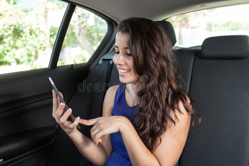 Jovem mulher no banco traseiro do carro que sorri e que lê o ebook imagens de stock