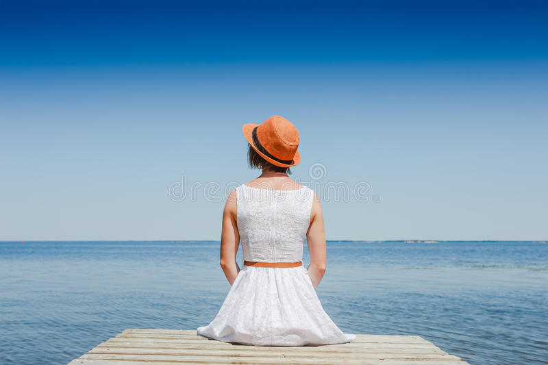 Jovem mulher no banho de sol branco do vestido no beira-mar foto de stock royalty free