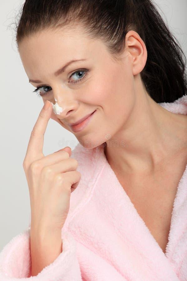 Jovem mulher no bathrobe cor-de-rosa que aplica um creme em seu nariz imagens de stock