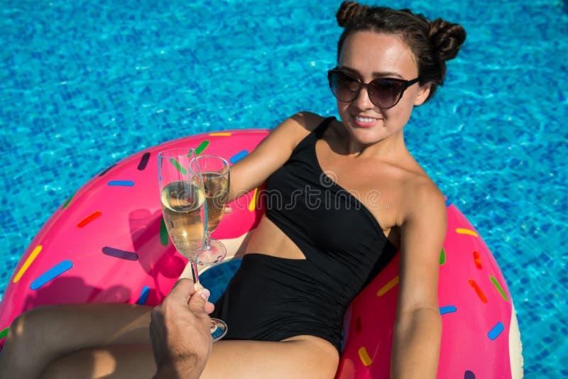 A jovem mulher no biquini e nos óculos de sol encontra-se no anel inflável colorido imagem de stock