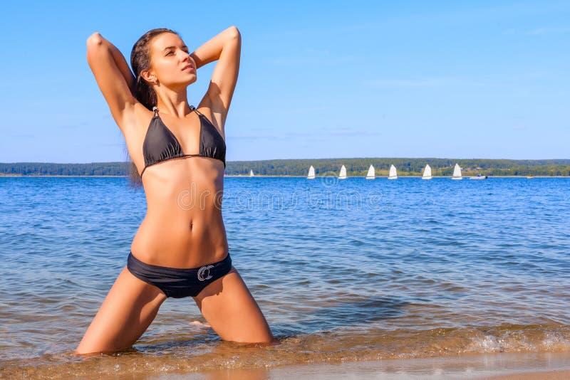 Jovem mulher no biquini em uma praia imagens de stock