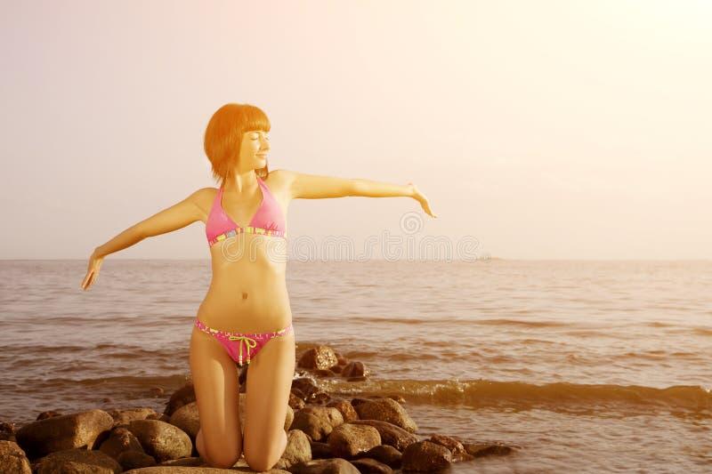 Jovem mulher no biquini na praia com suas suas mãos acima Menina com imagens de stock