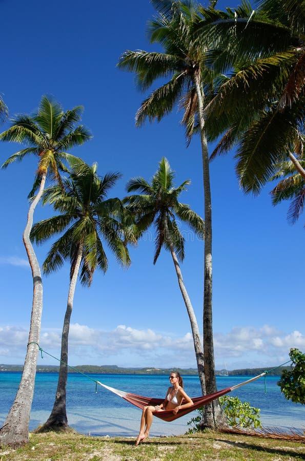 Jovem mulher no biquini que senta-se em uma rede entre palmeiras, O imagens de stock royalty free