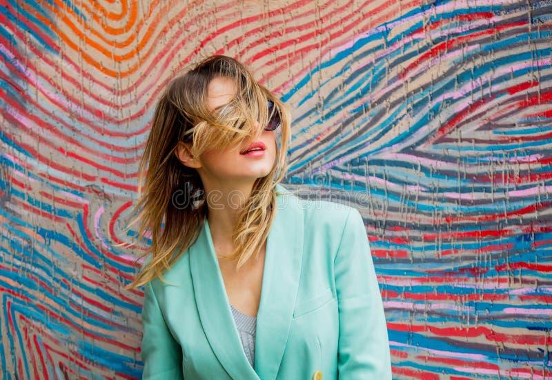 Jovem mulher no blazer do estilo 90s e dos óculos de sol fotografia de stock royalty free