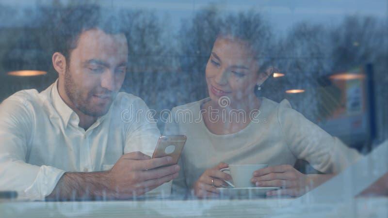 Jovem mulher no café que datilografa seu número de telefone para o homem considerável foto de stock royalty free