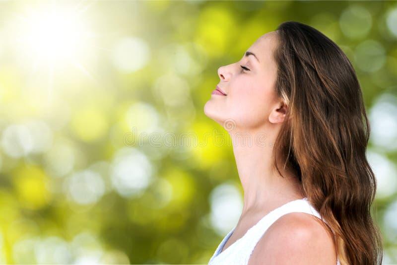 Jovem mulher no campo sob a luz do por do sol fotografia de stock royalty free