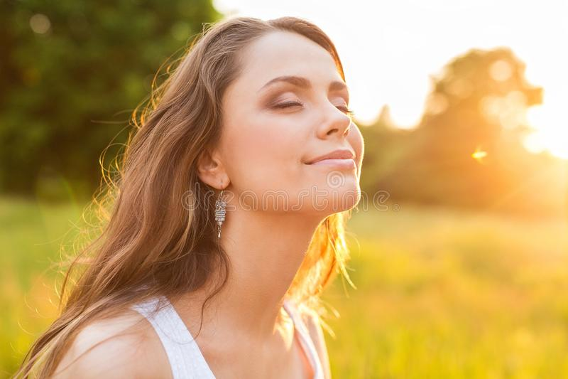 Jovem mulher no campo sob a luz do por do sol imagens de stock
