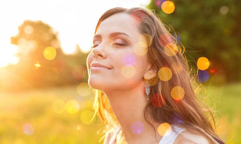Jovem mulher no campo sob a luz do por do sol fotos de stock royalty free
