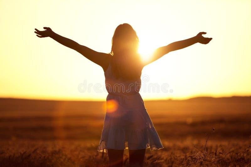 Jovem mulher no campo sob a luz do por do sol foto de stock
