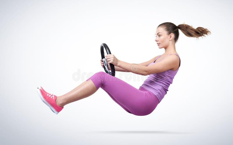Jovem mulher no carro cor-de-rosa do motorista do sportswear com volante, auto conceito imagens de stock royalty free