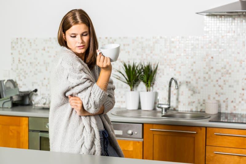 Jovem mulher no casaco de lã com a caneca de chá quente fotografia de stock royalty free