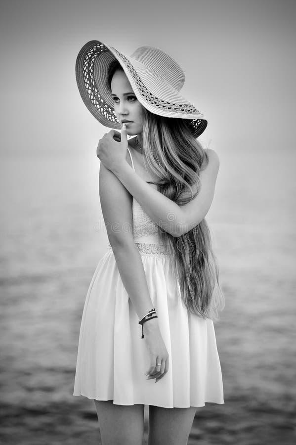 Jovem mulher no chapéu branco do vestido e de palha fotos de stock royalty free