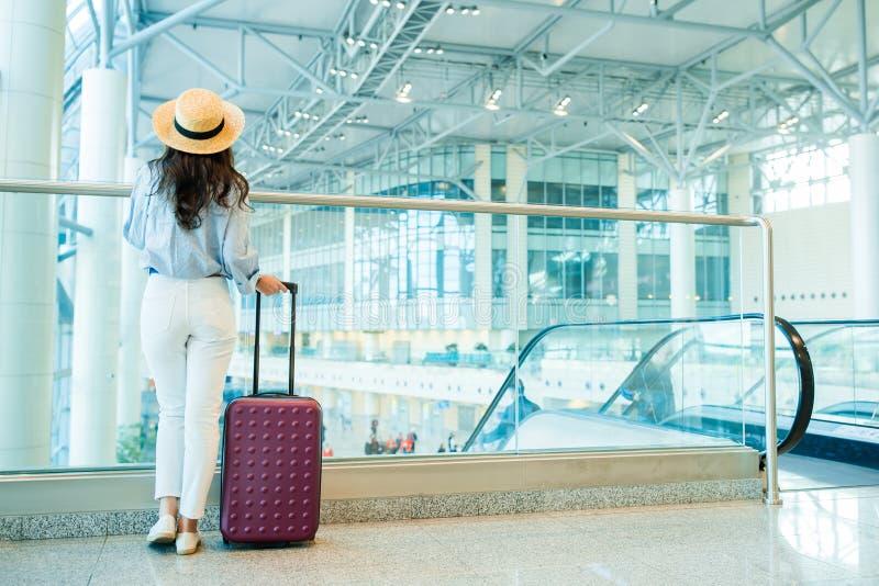 Jovem mulher no chapéu com bagagem no aeroporto internacional que anda com sua bagagem Passageiro da linha aérea em um aeroporto foto de stock