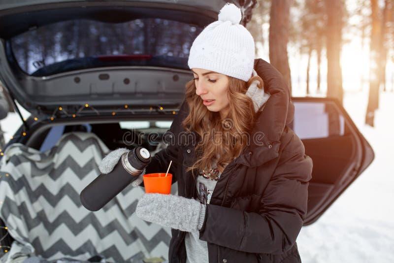 A jovem mulher no chapéu de lã e o revestimento preto estão o neartrunk do carro e das posses um o copo do chá quente em suas mão imagem de stock royalty free