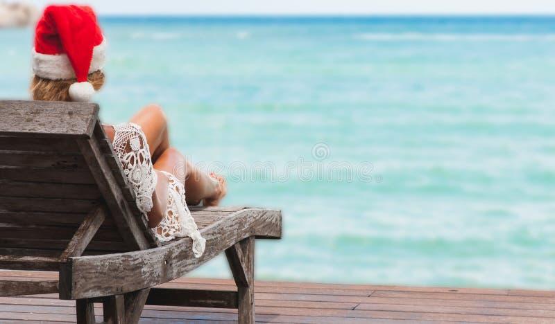 Jovem mulher no chapéu de Papai Noel que senta-se na sala de estar do chaise na praia tropical do mar imagem de stock royalty free