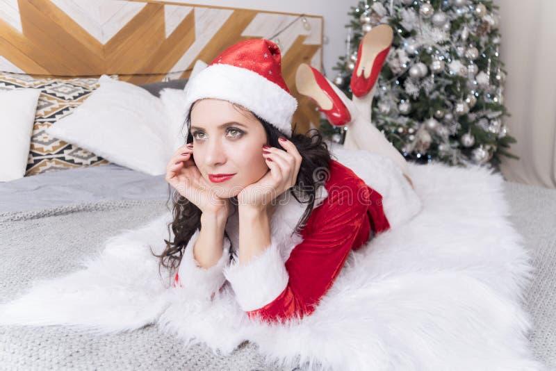Jovem mulher no chapéu de Santa que encontra-se na cama e que olha sonhadoramente para fora a janela no fundo de uma árvore de Na fotos de stock