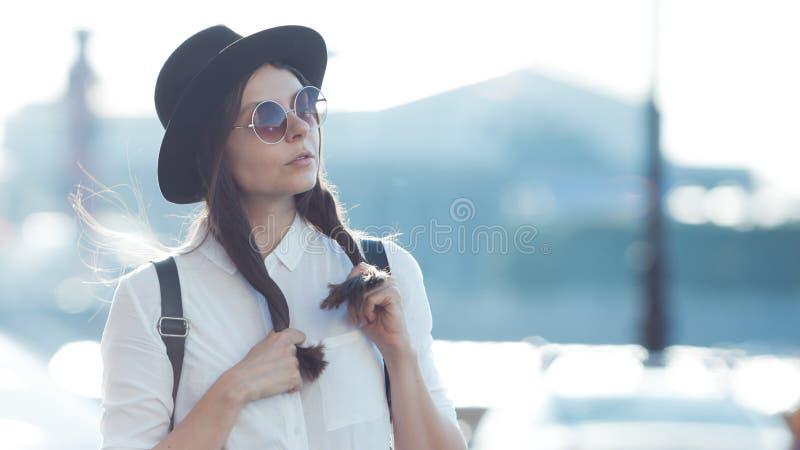 Jovem mulher no chapéu e em óculos de sol redondos que anda na cidade O turista da menina aprecia a caminhada foto de stock
