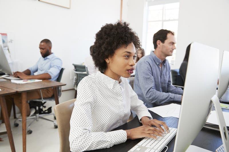 Jovem mulher no computador com os colegas no escritório de plano aberto fotos de stock royalty free