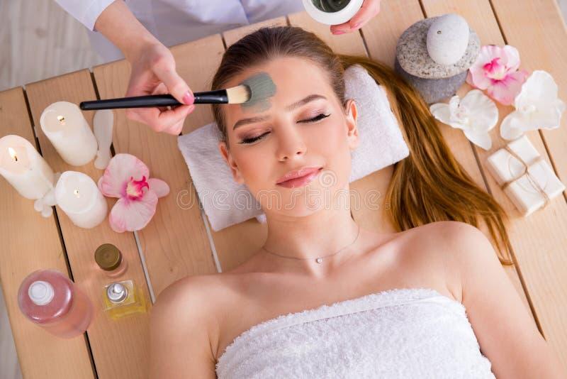A jovem mulher no conceito da saúde dos termas com máscara protetora foto de stock royalty free