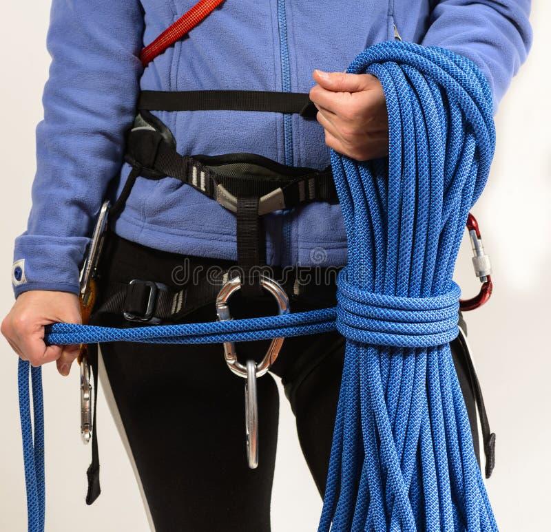 Jovem mulher no equipamento de escalada no fundo branco imagens de stock