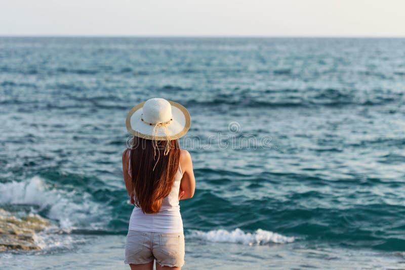 Jovem mulher no equipamento e no chapéu do verão pelo beira-mar imagens de stock royalty free