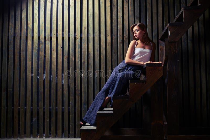 A jovem mulher no equipamento na moda está encontrando-se quase em escadas com mão imagens de stock