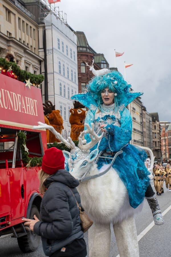 Jovem mulher no fantoche da equitação da parada do Natal de Hamburgo que sneaking acima no usuário do telefone celular imagem de stock royalty free