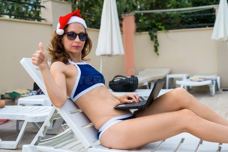 Jovem mulher no funcionamento do chapéu de Papai Noel no portátil pela associação, férias do Natal em um país tropical imagem de stock royalty free