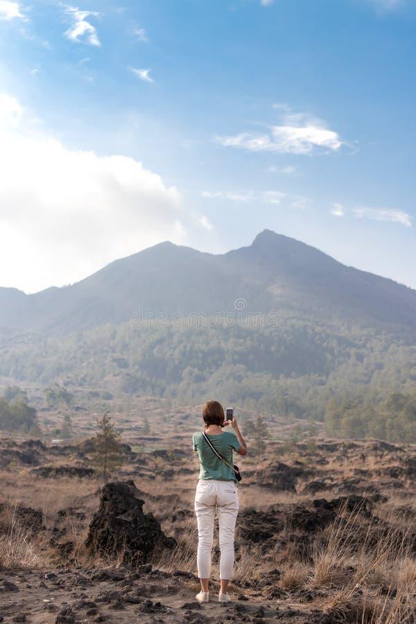 Jovem mulher no fundo de Batur do vulcão Ilha de Bali foto de stock royalty free