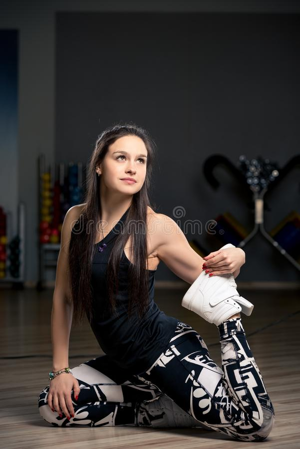 Jovem mulher no gym no assoalho que faz o esticão foto de stock
