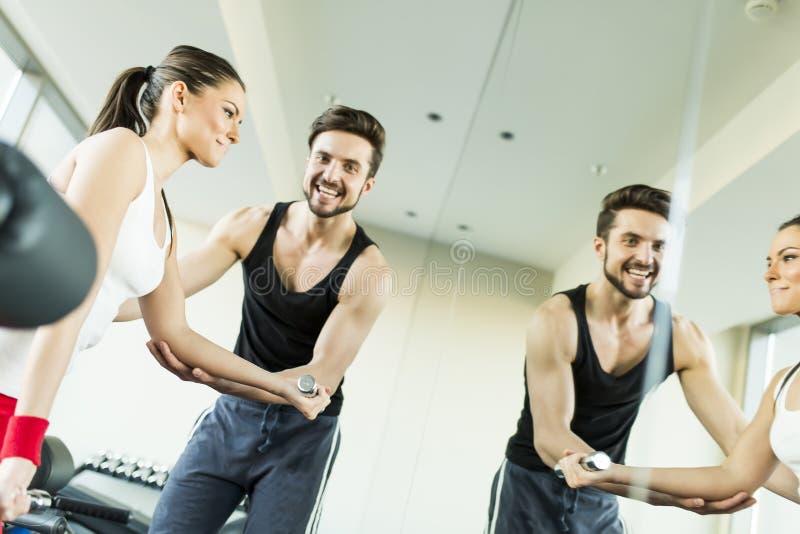 Jovem mulher no gym que exercita com seu instrutor pessoal foto de stock
