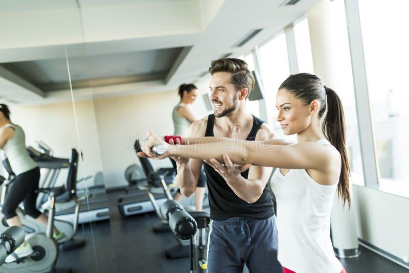 Jovem mulher no gym que exercita com seu instrutor pessoal fotos de stock