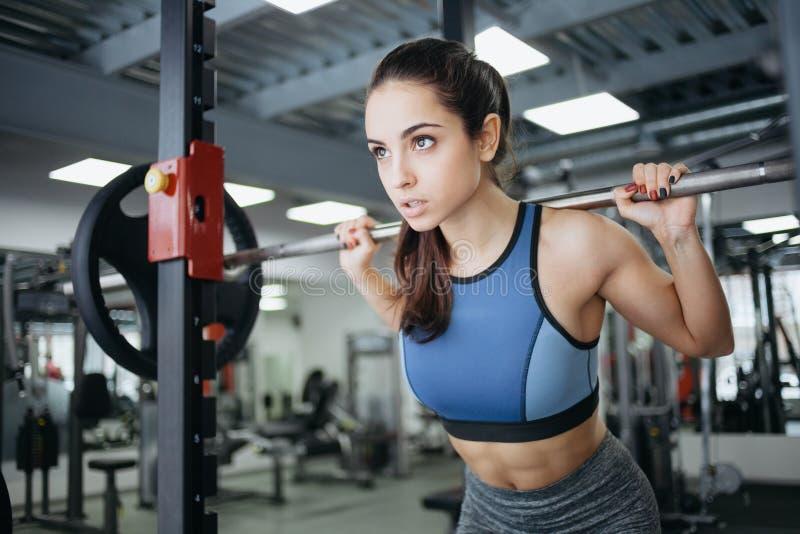 Jovem mulher no gym usando o equipamento da aptidão fotos de stock