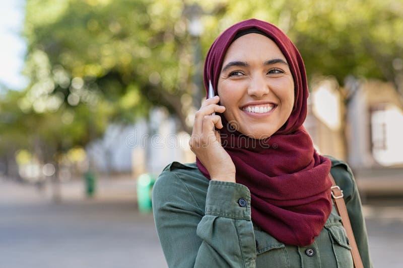 Jovem mulher no hijab que fala no telefone fotos de stock