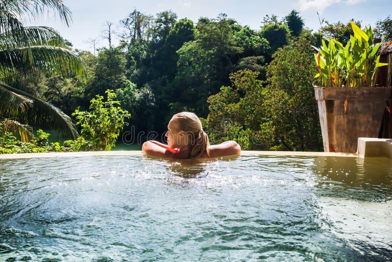 Jovem mulher no hotel de luxo na piscina fotos de stock royalty free