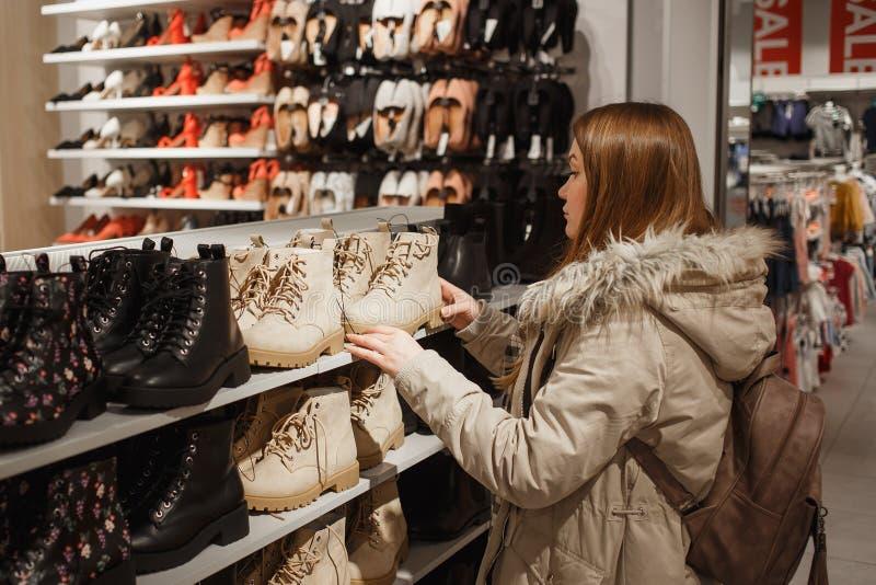 A jovem mulher no inverno bege veste a escolha de botas bege na moda do inverno na alameda fotos de stock