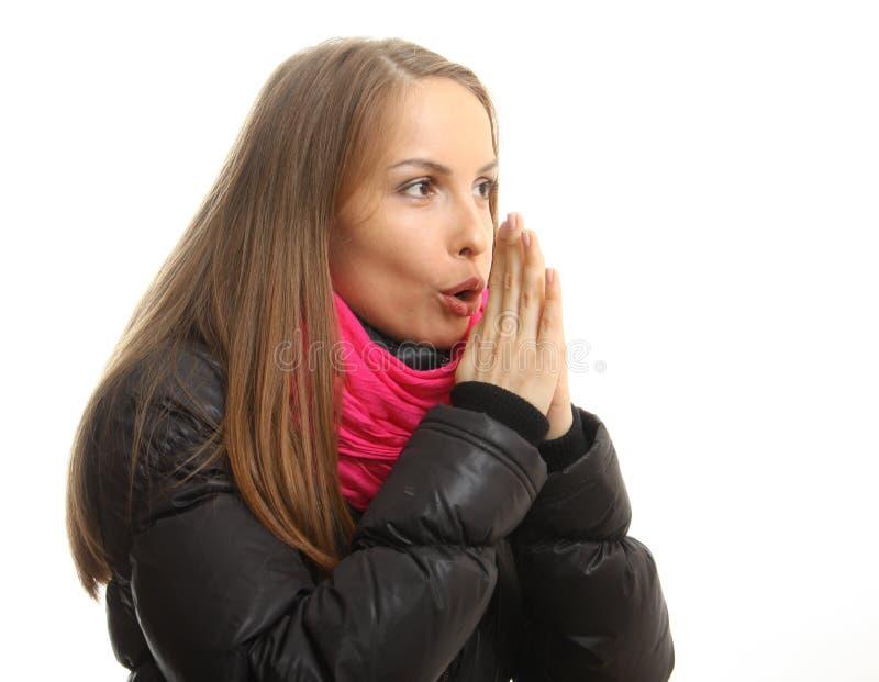 A jovem mulher no inverno tenta aquecer suas mãos foto de stock
