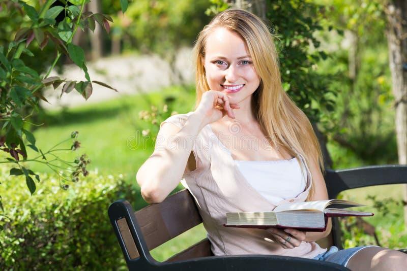 Jovem mulher no livro de leitura do banco fotografia de stock royalty free