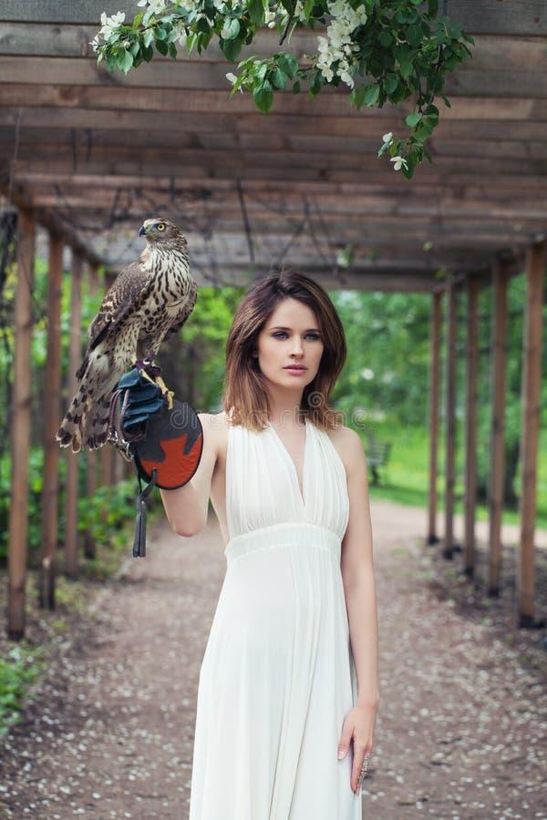 Jovem mulher no pássaro branco do falcão da terra arrendada do vestido exterior fotografia de stock royalty free