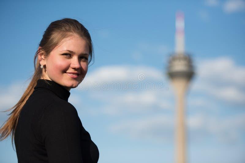 Jovem mulher no preto com torre da tevê fotos de stock