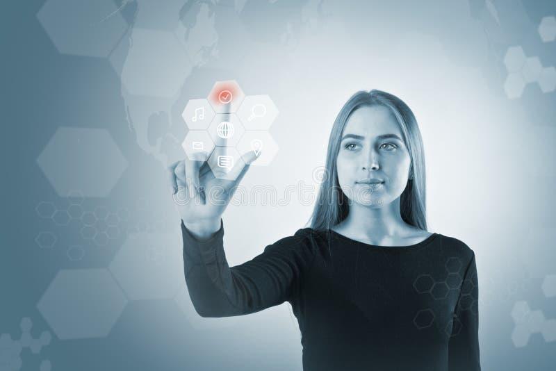 A jovem mulher no preto está empurrando o botão Conceito inovativo da tecnologia fotografia de stock