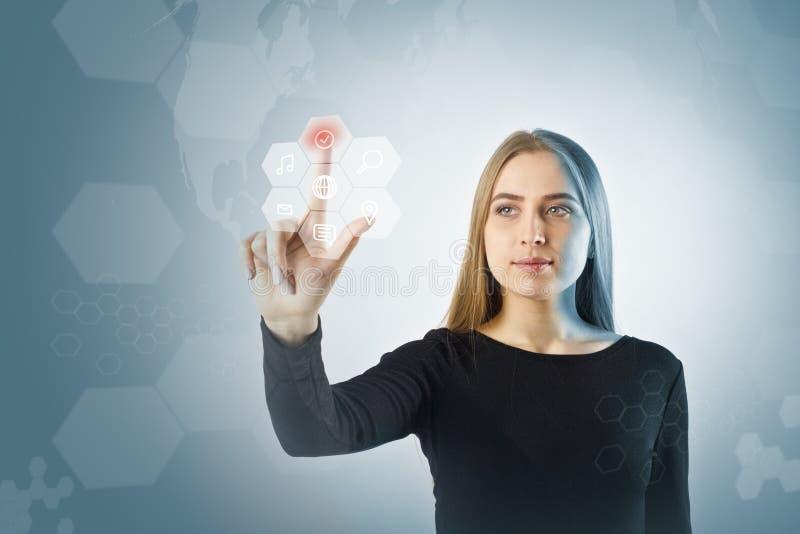 A jovem mulher no preto está empurrando o botão Conceito inovativo da tecnologia imagem de stock royalty free