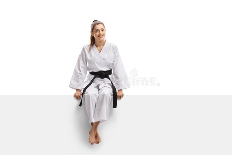 Jovem mulher no quimono e no cinturão negro que sentam-se em uma bandeira imagens de stock