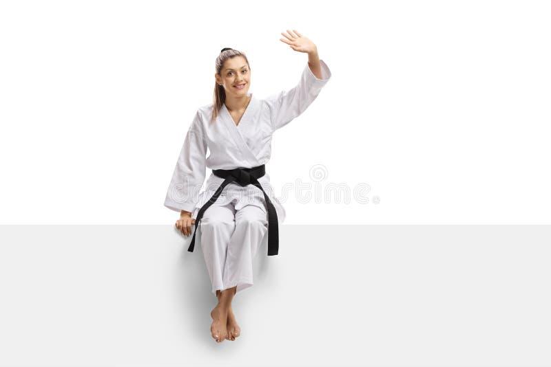 Jovem mulher no quimono que senta-se em um painel e em uma ondulação fotografia de stock royalty free