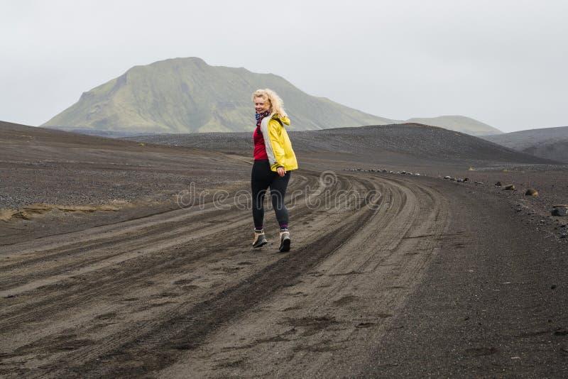 Jovem mulher no revestimento amarelo que corre no campo de lava preto na estrada à área de Landmannalaugar, Islândia imagem de stock royalty free