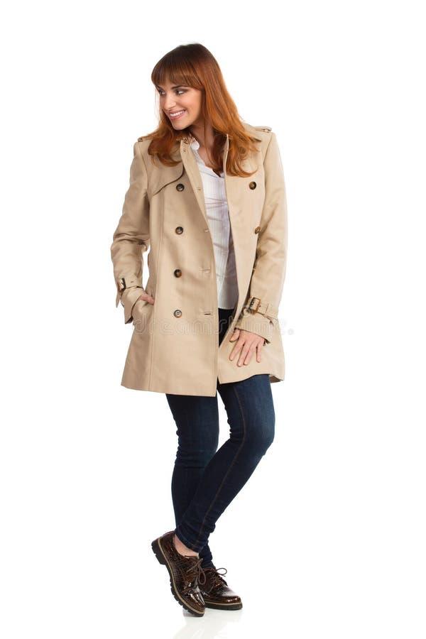 A jovem mulher no revestimento, em calças de brim e em sapatas bege de Brown é estando, de sorriso e de vista afastado fotos de stock royalty free