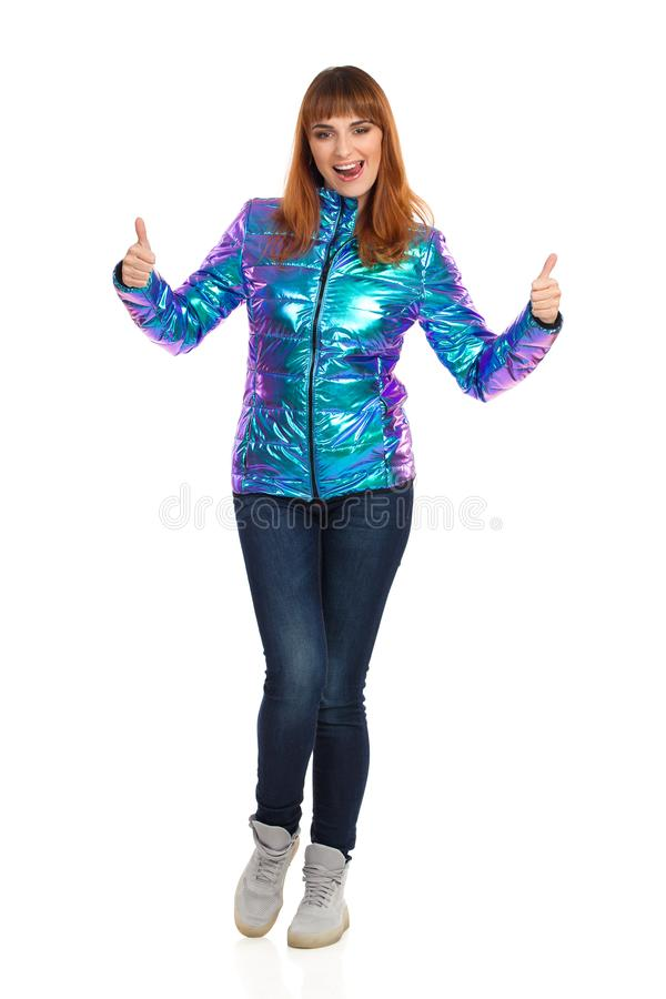 A jovem mulher no revestimento vibrante da pena está colando para fora a língua e está mostrando os polegares acima imagem de stock